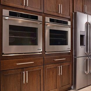 Modelo de cocina lineal, tradicional renovada, grande, abierta, con una isla, fregadero bajoencimera, armarios con paneles empotrados, puertas de armario de madera oscura, electrodomésticos de acero inoxidable y suelo de madera clara