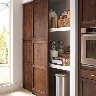 Modelo de cocina lineal, clásica renovada, grande, con una isla, fregadero bajoencimera, armarios con paneles empotrados, puertas de armario de madera oscura, electrodomésticos de acero inoxidable, suelo de madera clara, despensa y suelo beige