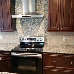 Idéer för stora vintage beige kök, med en undermonterad diskho, luckor med upphöjd panel, skåp i mörkt trä, rostfria vitvaror, en köksö, granitbänkskiva, flerfärgad stänkskydd, stänkskydd i keramik, ljust trägolv och gult golv