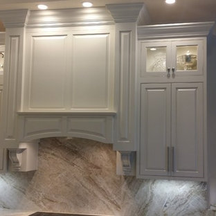 Mid-sized transitional kitchen designs - Mid-sized transitional u-shaped kitchen photo in Miami with an undermount sink, beaded inset cabinets, white cabinets, granite countertops, stone slab backsplash, stainless steel appliances and an island