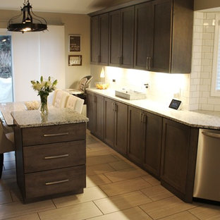 Mid-sized transitional enclosed kitchen ideas - Enclosed kitchen - mid-sized transitional l-shaped porcelain tile and gray floor enclosed kitchen idea in Detroit with a single-bowl sink, shaker cabinets, gray cabinets, granite countertops, white backsplash, ceramic backsplash, stainless steel appliances, an island and gray countertops