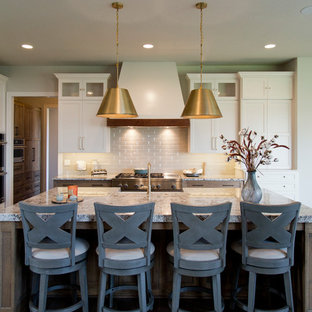 カンザスシティの大きいエクレクティックスタイルのおしゃれなキッチン (エプロンフロントシンク、シェーカースタイル扉のキャビネット、白いキャビネット、御影石カウンター、ベージュキッチンパネル、セラミックタイルのキッチンパネル、シルバーの調理設備、濃色無垢フローリング、茶色い床、グレーのキッチンカウンター) の写真