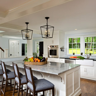 Photo of an expansive traditional l-shaped eat-in kitchen in Boston with a farmhouse sink, beaded inset cabinets, white cabinets, marble benchtops, grey splashback, marble splashback, stainless steel appliances, medium hardwood floors, with island, brown floor, grey benchtop and coffered.