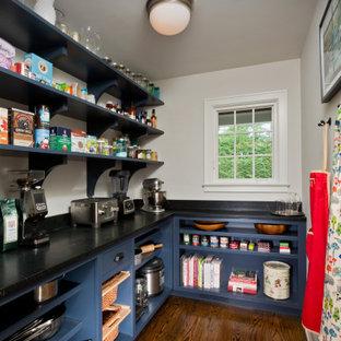 Expansive classic l-shaped kitchen pantry in Boston with blue cabinets, soapstone worktops, black splashback, medium hardwood flooring, no island, brown floors and black worktops.