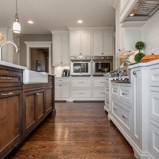 シカゴの広いトラディショナルスタイルのおしゃれなキッチン (エプロンフロントシンク、インセット扉のキャビネット、白いキャビネット、ガラスカウンター、白いキッチンパネル、サブウェイタイルのキッチンパネル、シルバーの調理設備、濃色無垢フローリング、茶色い床、ターコイズのキッチンカウンター) の写真
