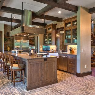 Foto på ett rustikt brun l-kök, med en rustik diskho, skåp i shakerstil, skåp i mellenmörkt trä, rostfria vitvaror, tegelgolv, en köksö och grått golv