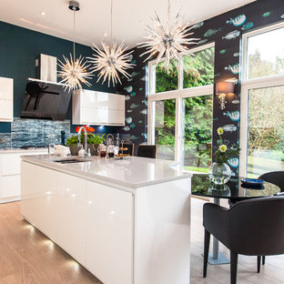 Contemporary kitchen/diner in Other with an island, flat-panel cabinets, white cabinets, blue splashback, glass tiled splashback and light hardwood flooring.