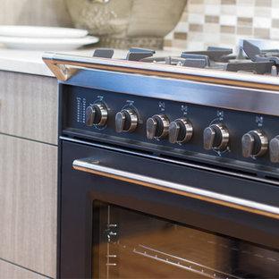 Bild på ett mellanstort vintage kök, med släta luckor, beige skåp, bänkskiva i kvarts, beige stänkskydd, stänkskydd i glaskakel och svarta vitvaror