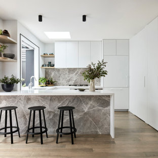 Inspiration for a mid-sized contemporary u-shaped kitchen in Melbourne with an undermount sink, flat-panel cabinets, white cabinets, quartz benchtops, grey splashback, stone slab splashback, medium hardwood floors, a peninsula, brown floor, white benchtop and panelled appliances.