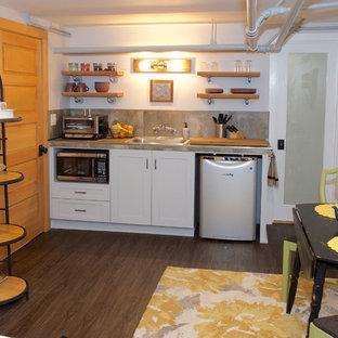 ポートランドの小さいエクレクティックスタイルのおしゃれなキッチン (ドロップインシンク、シェーカースタイル扉のキャビネット、白いキャビネット、タイルカウンター、グレーのキッチンパネル、石タイルのキッチンパネル、シルバーの調理設備の、クッションフロア、アイランドなし、茶色い床、グレーのキッチンカウンター) の写真