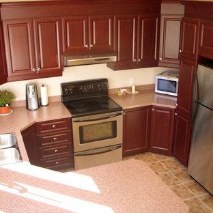 Exempel på ett mellanstort, avskilt klassiskt röd rött u-kök, med en dubbel diskho, rostfria vitvaror, klinkergolv i keramik, luckor med upphöjd panel, röda skåp, granitbänkskiva, en halv köksö och brunt golv