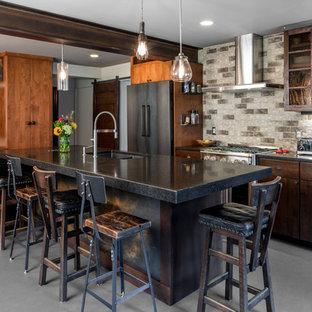 Große, Einzeilige Moderne Wohnküche mit Doppelwaschbecken, Glasfronten, Küchenrückwand in Grau, schwarzen Elektrogeräten, Kücheninsel, dunklen Holzschränken, Granit-Arbeitsplatte, Rückwand aus Steinfliesen und Betonboden in Minneapolis