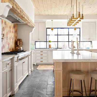 Inspiration for a large farmhouse l-shaped black floor and slate floor kitchen remodel in Dallas with shaker cabinets, white cabinets, an island, multicolored backsplash, white countertops, a farmhouse sink, quartz countertops, stainless steel appliances and window backsplash