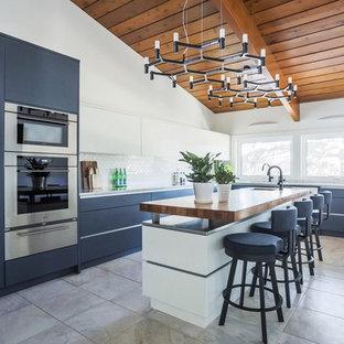 Idee per una cucina a L moderna di medie dimensioni con ante lisce, ante blu, top in legno, paraspruzzi bianco, elettrodomestici in acciaio inossidabile, pavimento con piastrelle in ceramica, isola e pavimento grigio