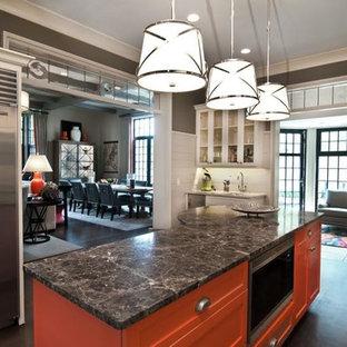 チャールストンの中サイズのエクレクティックスタイルのおしゃれなキッチン (アンダーカウンターシンク、ガラス扉のキャビネット、白いキャビネット、ソープストーンカウンター、白いキッチンパネル、木材のキッチンパネル、シルバーの調理設備の、黒い床) の写真