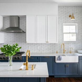Idées déco pour une cuisine classique avec un évier de ferme, un plan de travail en quartz modifié, une crédence blanche, un électroménager en acier inoxydable, un îlot central, un sol marron, un plan de travail blanc, un placard à porte shaker, des portes de placard bleues, une crédence en carrelage métro et un sol en bois foncé.