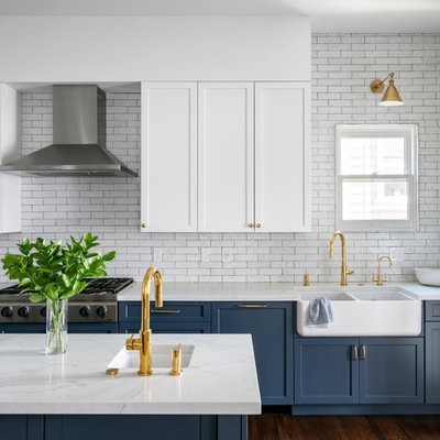 Kitchen - transitional brown floor and dark wood floor kitchen idea in San Francisco with a farmhouse sink, quartz countertops, white backsplash, stainless steel appliances, an island, white countertops, shaker cabinets, blue cabinets and subway tile backsplash