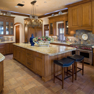 Photo of a large mediterranean u-shaped open plan kitchen in Orlando with raised-panel cabinets, medium wood cabinets, multi-coloured splashback, stainless steel appliances, granite benchtops, ceramic floors, with island and slate splashback.