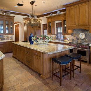オーランドの大きい地中海スタイルのおしゃれなキッチン (レイズドパネル扉のキャビネット、中間色木目調キャビネット、マルチカラーのキッチンパネル、シルバーの調理設備、御影石カウンター、セラミックタイルの床、スレートのキッチンパネル) の写真