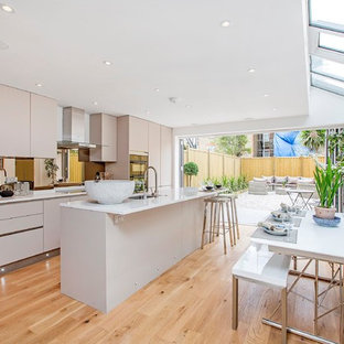 Photo of a large contemporary single-wall open plan kitchen in London with flat-panel cabinets, grey cabinets, quartz worktops, mirror splashback, stainless steel appliances, light hardwood flooring, an island and a submerged sink.