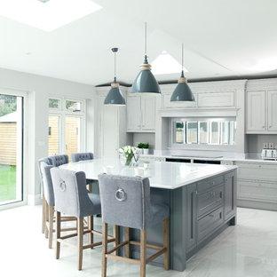 他の地域のトランジショナルスタイルのおしゃれなアイランドキッチン (落し込みパネル扉のキャビネット、グレーのキャビネット、ミラータイルのキッチンパネル、グレーの床、グレーのキッチンカウンター) の写真