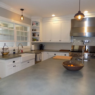 Large contemporary eat-in kitchen ideas - Eat-in kitchen - large contemporary u-shaped medium tone wood floor eat-in kitchen idea in Columbus with a farmhouse sink, recessed-panel cabinets, white cabinets, concrete countertops, white backsplash, ceramic backsplash, stainless steel appliances and an island
