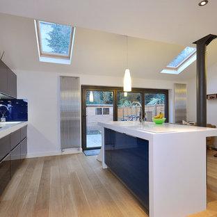 Exempel på ett modernt kök med öppen planlösning, med släta luckor, blått stänkskydd och glaspanel som stänkskydd