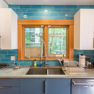 Idée de décoration pour une cuisine américaine design en U de taille moyenne avec un évier encastré, un placard à porte plane, des portes de placard blanches, un plan de travail en stéatite, une crédence bleue, une crédence en carrelage métro, un électroménager en acier inoxydable, un sol en ardoise, un îlot central, un sol gris et un plan de travail noir.