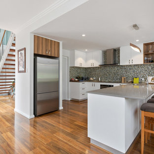 Inspiration for a transitional u-shaped kitchen in Perth with an undermount sink, flat-panel cabinets, white cabinets, grey splashback, mosaic tile splashback, stainless steel appliances, medium hardwood floors, brown floor and grey benchtop.