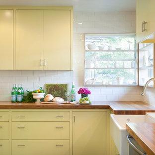 オースティンのコンテンポラリースタイルのおしゃれな独立型キッチン (エプロンフロントシンク、木材カウンター、フラットパネル扉のキャビネット、黄色いキャビネット、白いキッチンパネル、サブウェイタイルのキッチンパネル) の写真