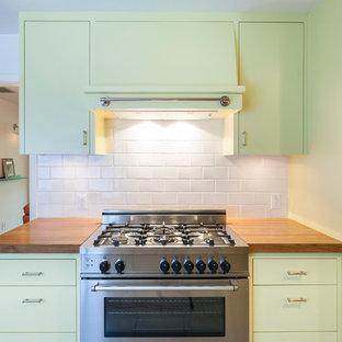 Idéer för ett modernt kök, med träbänkskiva, gula skåp, släta luckor, vitt stänkskydd, stänkskydd i tunnelbanekakel och rostfria vitvaror