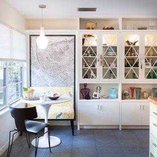 Bild på ett funkis kök, med luckor med glaspanel, träbänkskiva och gula skåp