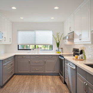 Photo of a mid-sized traditional u-shaped separate kitchen in Vancouver with a double-bowl sink, raised-panel cabinets, grey cabinets, quartz benchtops, white splashback, subway tile splashback, stainless steel appliances and no island.