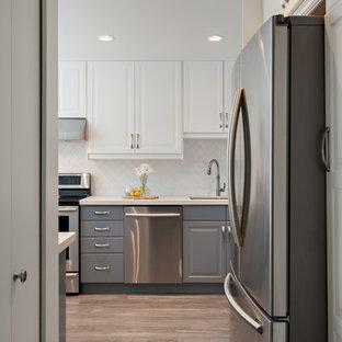 Klassisk inredning av ett avskilt, mellanstort u-kök, med en dubbel diskho, luckor med upphöjd panel, grå skåp, bänkskiva i kvarts, vitt stänkskydd, stänkskydd i tunnelbanekakel och rostfria vitvaror