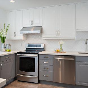 Exempel på ett avskilt, mellanstort klassiskt u-kök, med en dubbel diskho, luckor med upphöjd panel, grå skåp, bänkskiva i kvarts, vitt stänkskydd, stänkskydd i tunnelbanekakel och rostfria vitvaror