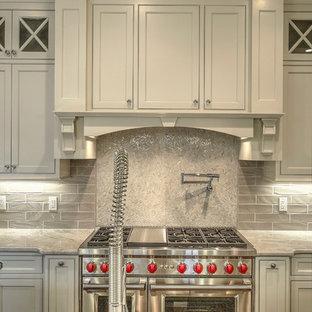 Inredning av ett klassiskt kök, med en undermonterad diskho, skåp i shakerstil, beige skåp, bänkskiva i kvartsit, beige stänkskydd, stänkskydd i keramik, rostfria vitvaror, mellanmörkt trägolv och flera köksöar