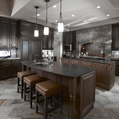 Example of a classic kitchen design in Calgary with raised-panel cabinets, dark wood cabinets, gray backsplash and paneled appliances