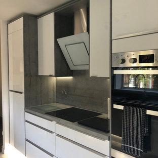 グラスゴーの中くらいのコンテンポラリースタイルのおしゃれなダイニングキッチン (一体型シンク、フラットパネル扉のキャビネット、白いキャビネット、ラミネートカウンター、グレーのキッチンパネル、木材のキッチンパネル、シルバーの調理設備、クッションフロア、アイランドなし、グレーの床、グレーのキッチンカウンター) の写真