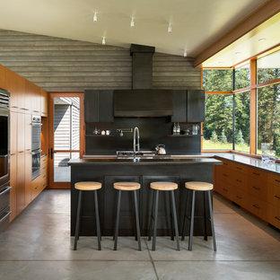 Idee per una cucina minimal di medie dimensioni con ante lisce, ante in legno scuro, top in acciaio inossidabile, paraspruzzi nero, paraspruzzi con piastrelle di metallo, elettrodomestici in acciaio inossidabile, pavimento in cemento, isola, pavimento grigio e top grigio