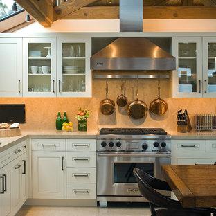 Foto de cocina costera con armarios tipo vitrina, electrodomésticos de acero inoxidable y salpicadero de piedra caliza