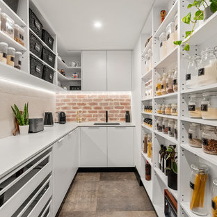 Design ideas for a contemporary kitchen pantry in Perth with an undermount sink, open cabinets, white cabinets, beige splashback, brown floor, white benchtop and brick splashback.