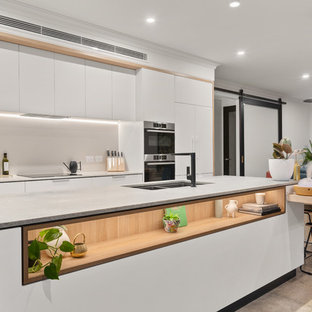 Design ideas for a contemporary open plan kitchen in Perth with a double-bowl sink, flat-panel cabinets, white cabinets, grey splashback, stainless steel appliances, with island, white benchtop and brown floor.