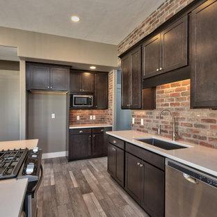 他の地域の中サイズのコンテンポラリースタイルのおしゃれなキッチン (アンダーカウンターシンク、落し込みパネル扉のキャビネット、濃色木目調キャビネット、ラミネートカウンター、マルチカラーのキッチンパネル、レンガのキッチンパネル、シルバーの調理設備の、無垢フローリング、マルチカラーの床、白いキッチンカウンター) の写真