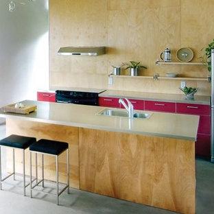 Offene, Einzeilige, Mittelgroße Moderne Küche mit roten Schränken, Edelstahl-Arbeitsplatte, Küchenrückwand in Braun, Rückwand aus Holz, schwarzen Elektrogeräten, Betonboden, Kücheninsel, grauem Boden und grauer Arbeitsplatte in Ottawa