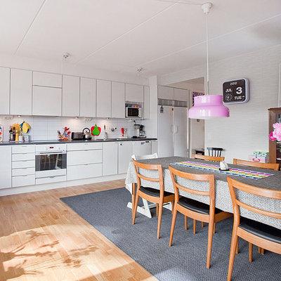 Mid-sized danish single-wall medium tone wood floor eat-in kitchen photo in Stockholm with flat-panel cabinets, white cabinets, white backsplash, white appliances, a single-bowl sink, subway tile backsplash and no island