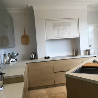 Photo of a medium sized contemporary l-shaped kitchen/diner in Manchester with a built-in sink, flat-panel cabinets, grey cabinets, laminate countertops, black appliances, limestone flooring, an island and beige floors.
