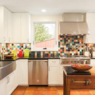 ニューヨークの中くらいのモダンスタイルのおしゃれなキッチン (エプロンフロントシンク、シェーカースタイル扉のキャビネット、白いキャビネット、人工大理石カウンター、マルチカラーのキッチンパネル、モザイクタイルのキッチンパネル、シルバーの調理設備、テラコッタタイルの床、赤い床) の写真