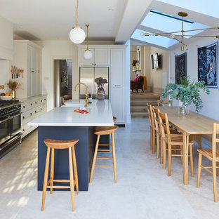 Design ideas for a classic l-shaped kitchen/diner in London with a belfast sink, shaker cabinets, white cabinets, white splashback, stainless steel appliances, an island, beige floors and white worktops.