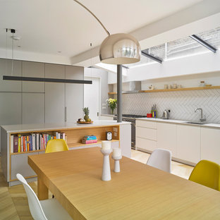 Inspiration for a medium sized contemporary single-wall kitchen/diner in London with a submerged sink, flat-panel cabinets, white cabinets, white splashback, metro tiled splashback, integrated appliances, light hardwood flooring, an island and beige floors.