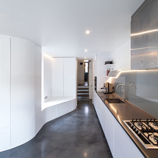 This is an example of a large contemporary single-wall kitchen in London with flat-panel cabinets, white cabinets, composite countertops, grey splashback, concrete flooring, grey floors, grey worktops, a single-bowl sink, glass sheet splashback and no island.